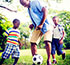 man playing soccer and kids
