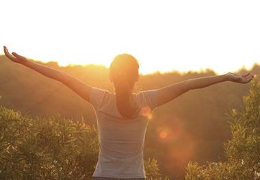 woman with arms up facing sun