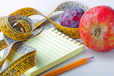 notepad, pencil, tape measure and fruit