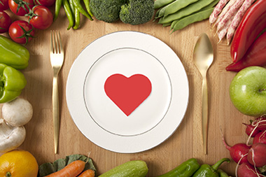 fruits and veggies surround a plate with a heart
