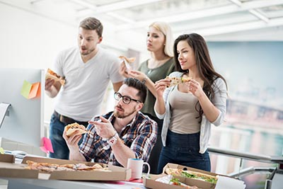 people eating pizza at office