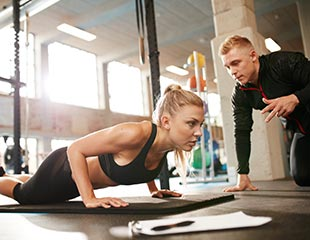 Woman doing pushups with trainer