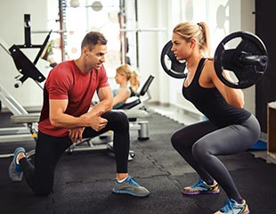Woman doing squats with trainer