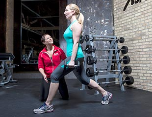 Woman doing lunges with trainer
